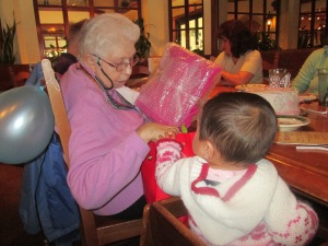 Helping great-grandma open presents at her 84th birthday party